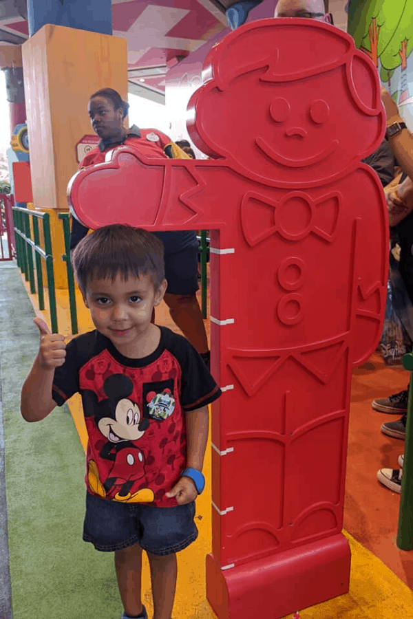 child in front of slinky dog dash sign