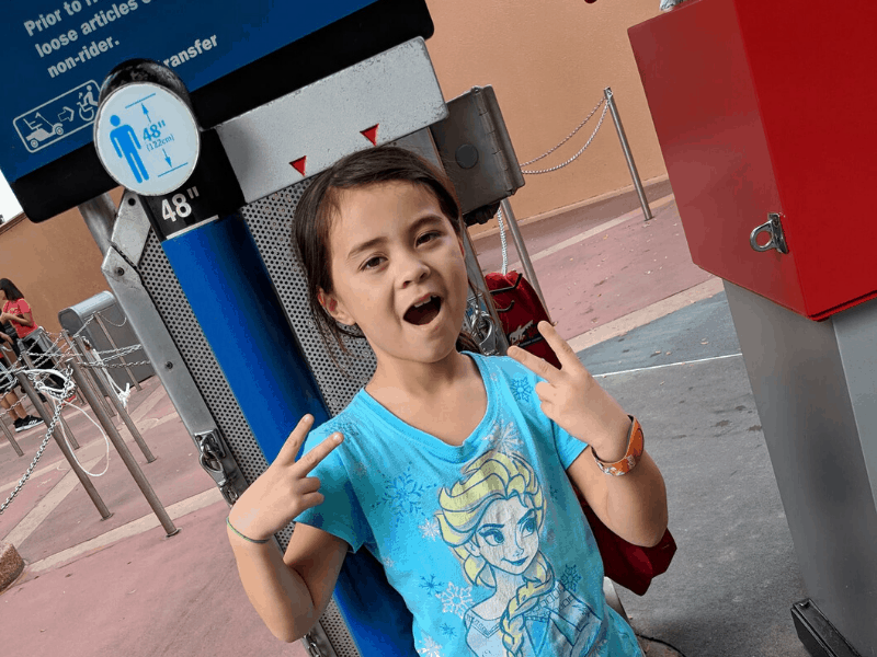 child in front of Disney height sign