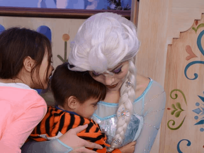 small boy getting hugged by Elsa