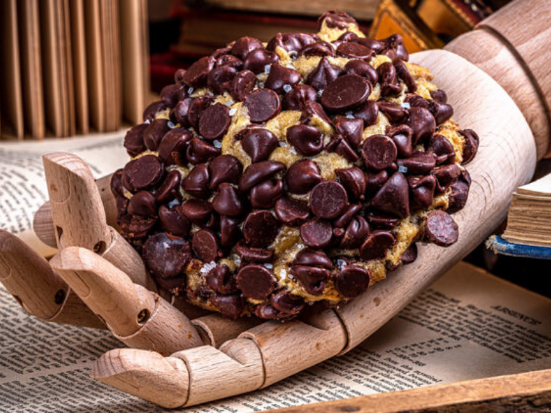 huge loaded chocolate chip cookie on wooden hand