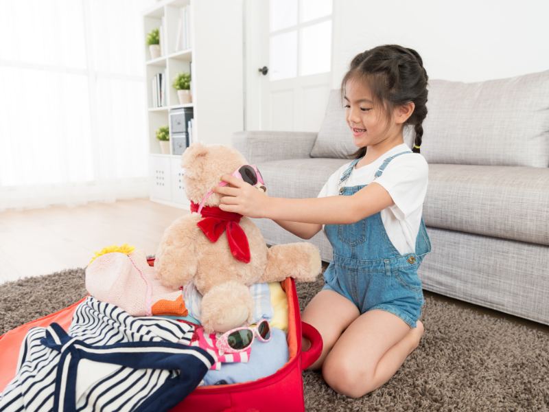 girl putting sunglasses on bear sitting on an open suitcase