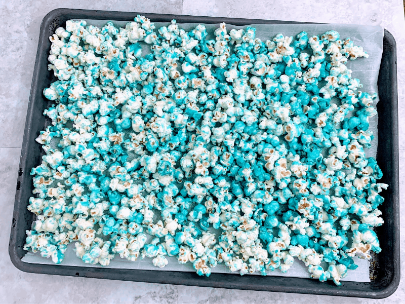 blue popcorn on parchment lined baking sheet
