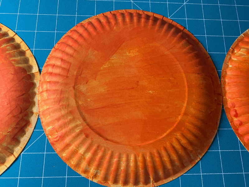 orange painted paper plates on cutting mat