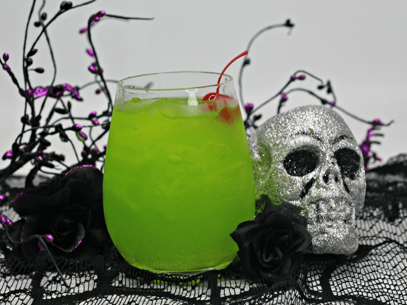 Green drink n clear glass next to glittery skull decor