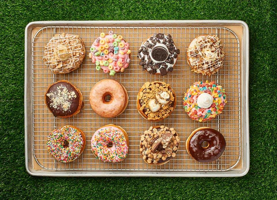 Tray of assorted donuts on green astro turf