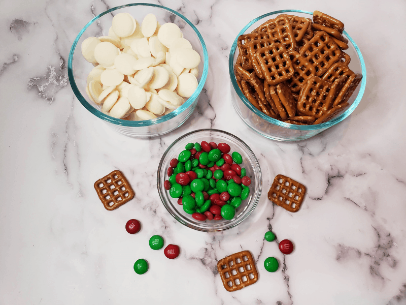 clear glass bowls each filled with white chocolate melts, pretzels, and red & green M&ms
