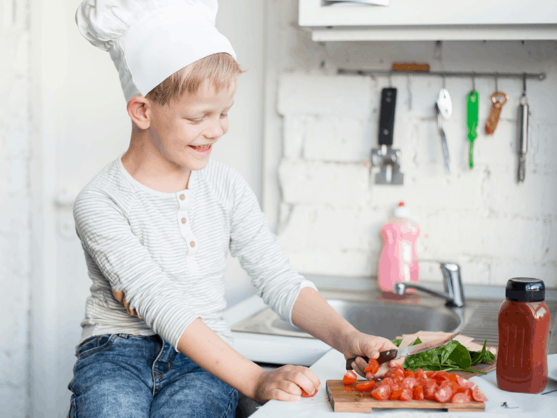 kids in chef hat cutting tomatoes