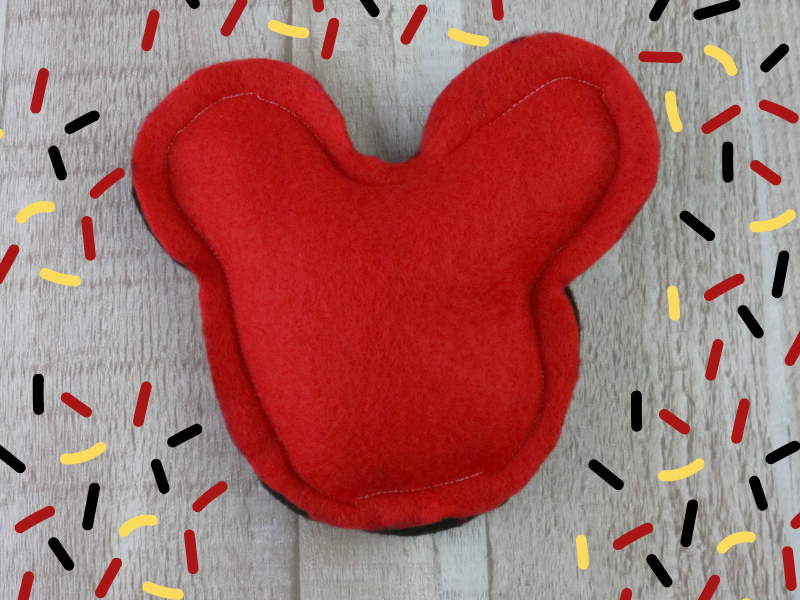 DIY Mickey Mouse Cold Pack on wood background with red, yellow, and black confetti