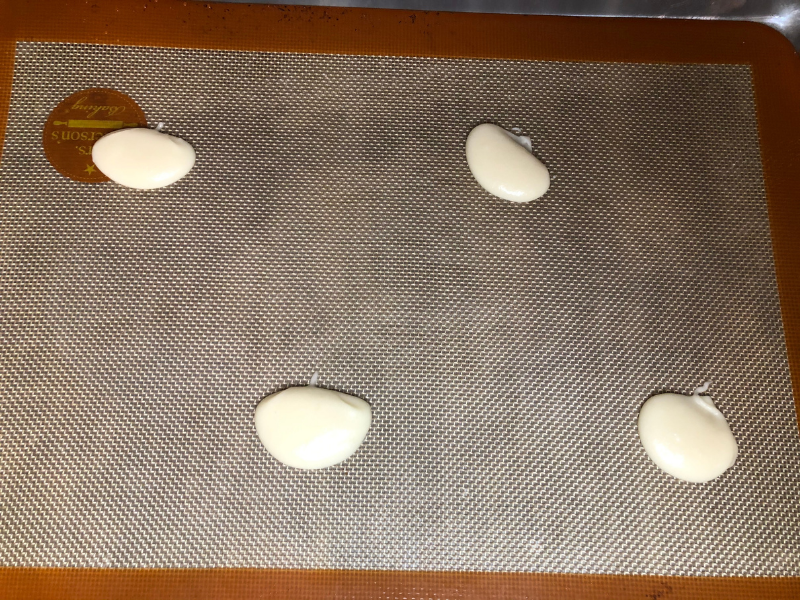 spooned cookie batter on cookie sheet with silpat