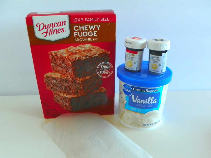 box of brownie mix, vanilla frosting tub, black and red food coloring, clear pastry bag