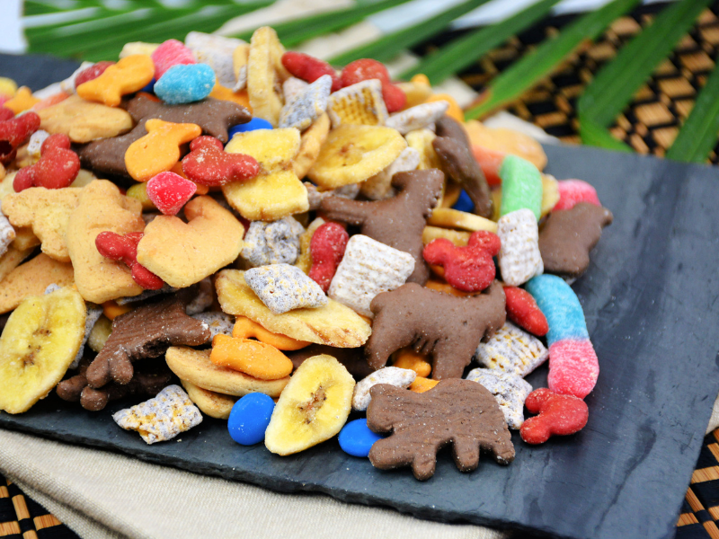 Jungle cruise snack mix on black plate with palm leaf in background